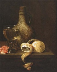 a stil life of a flagon, a wineglass, grapes and a peeled lemon by gillis jacobz van hulsdonck