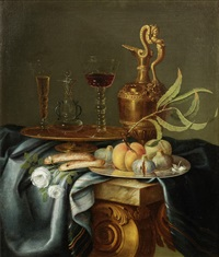 a still life of an elaborate gilt ewer beside two glasses of wine and a carafe on a gilt dish with white roses, biscuits and a silver dish of fruit on a table draped with a blue cloth by maximilian pfeiler