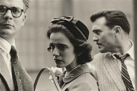a woman on the street with two men nyc by diane arbus