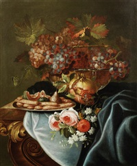 a still life of a glass bowl of grapes, a pomegranate, a silver dish of biscuits and fruit, with flowers on a table draped with a blue cloth by maximilian pfeiler