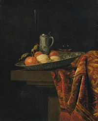 still life of fruit in a blue and white porcelain bowl with other objects resting on a stone ledge draped with an oriental carpet by hendrick van streeck