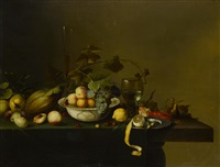 a still life with fruit, goblet and lobster on a wooden table by michiel simons