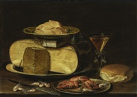 slices of butter on a wanli 'kraak' porcelain dish, a stack of cheese on a pewter plate, with a jug, a façon-de-venise wineglass, a bun, crayfish on a pewter plate, a knife and shrimp on a table by clara peeters