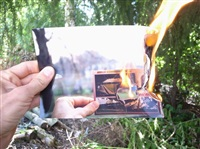 hand holding burning photograph of the arnold schwarzenegger stadium on fire by jonathan monk