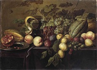 plums, peaches, grapes, melons, a half pomegranate, and a peeled lemon in a glass, all on a partially draped table by michiel simons