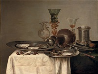 oysters and hazelnuts on pewter dishes, a roemer in a bekerschroef, a silver salt cellar and an earthenware jug, all on a partly draped table by cornelisz mahu