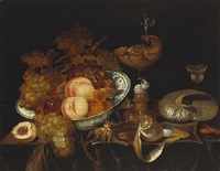 a still life of fruit in a blue and white bowl, a ewer, a goblet, a partially-peeled lemon and a nautilus shell, all resting on a partially draped table by bartholomeus assteyn