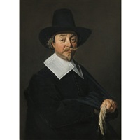 portrait of a man, in black, wearing a hat and holding a pair of gloves by frans hals the elder