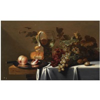 still life with blue and white grapes, chestnuts, a loaf of bread, peaches and a knife on a pewter plate, with a peeled lemon in a roemer, all arranged on a partly draped table by michiel simons
