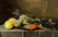 a still life with two finches, a kingfisher, grapes, peaches, prunes and a façon-de-venise wineglass, all on a draped table by pieter van overschee