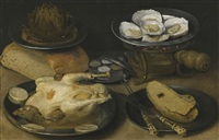 still life with a dish of oysters upon a brazier, an artichoke in a dish resting upon a loaf of bread, together with a cooked capoon and a knife, fork and slices of bread on plates and a silver condiment dish upon a table top by georg flegel