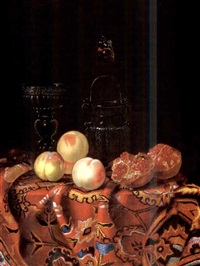 peaches, pomegranates, a venetian glass and a glass vessel with a butterfly nearby, on a carpeted table by johannes borman