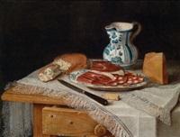 ein tisch mit weißer, fransenbesetzter decke, darauf eine platte mit wurst und speck, brot, käse, ein weinkrug und ein messer by christian berentz