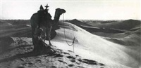 man on sand dunes with camel by rudolf lehnert