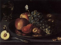 apples, pears, peaches and white grapes on a plate with a roemer of white wine, a sliced peach, a knife and a nut on a ledge with two butterflies by clara peeters