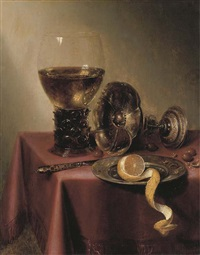 an upturned silver tazza, hazelnuts, a peeled lemon on a pewter platter, a knife and a roemer, on a draped table by maerten boelema de stomme
