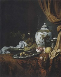 a blue and white facetted vase, a rose and walnuts on a pewter plate, a wanli kraak porselein bowl, a silver wine cooler, a wineglass, a glass, a lemon and roses on a table draped with a carpet by simon luttichuys