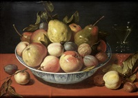 apples, pears, plums and other fruit with walnuts in a wan-li kraak ware bowl on a draped table-top, with a glass of wine by david ryckaert iii