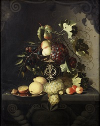 peaches and grapes draped over a silver tazza with lemons, oranges and apricots on a stone ledge by laurens craen