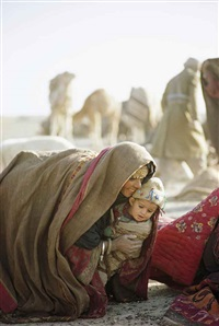 a kuchi woman lifts a young child, afghanistan by thomas j. abercrombie