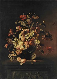 roses, poppies, sunflowers, tulips, peonies and other flowers in a glass vase, on a stone ledge with a frieze depicting putti playing with a goat by simon pietersz verelst
