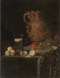 a gilt ewer, a roemer of beer, peaches, a partly-peeled lemon on a pewter tray, and grapes and peaches in a porcelain dish on a partly-draped table by georg hainz