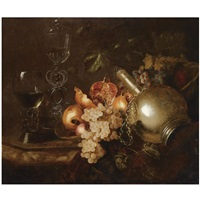 a still life of pomegranates, grapes, a silver vessel, a roemer and a venetian glass on a marble table draped with a cloth by barend van der meer