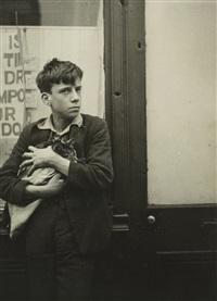 garçon avec un chat dans les bras appuyé contre une vitrine by dora maar
