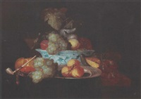 a still life with grapes, peaches and figs in a wan-li bowl, apricots on a pewter plate with grapes, a crab, a bun, a pipe and a glass, all on a draped table by thomas mertens