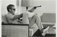 steve mcqueen aims a revolver in his living room by john dominis