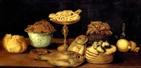 still life of bread, nuts in a bowl, pastries in a tazza, fish, garlic, cones in a basket and lemons, on a table by paul karslake