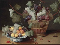 grapes, peaches and plums on a delft platter and grapes in a woven basket, with strawberries, cherries and a fly on a stone ledge by isaac soreau