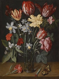 a still life with tulips, daffodils, carnations and other flowers in a vase, all resting on a wooden ledge with butterflies and a fly by jacob van hulsdonck