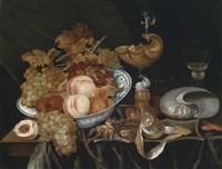 prunkstillleben, eine schale mit früchten, ein nautiluspokal und eine umgestürzte muschel by bartholomeus assteyn