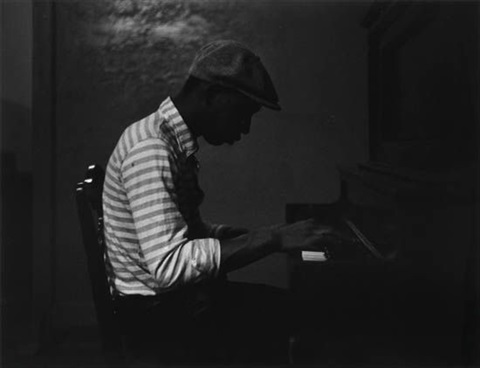 man in striped shirt at the piano by roy decarava