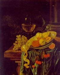 stilleben mit weintrauben, einer zitrone sowie anderen früchten in einer porzellanschale und einem gefüllten weinglas auf einem tisch by jacobus van der hagen