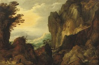 a rocky landscape with travellers on a path and crossing a bridge by a waterfall by joos de momper the elder