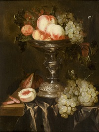 still life with peaches and grapes in a silver taza on a draped table by abraham van beyeren
