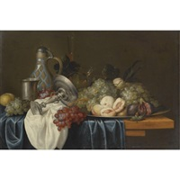 still life with bunches of grapes, peaches and figs on a pewter dish, together with a silver beaker and tazza, a wine glass, a flute and a stoneware jug, on a table draped with blue and white cloths by alexander coosemans
