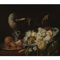 still life of grapes and other fruits in a wan-li porcelain bowl with a nautilus shell drinking glass by georg hainz