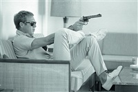 steve mcqueen aims a pistol in his living room, palm springs by john dominis