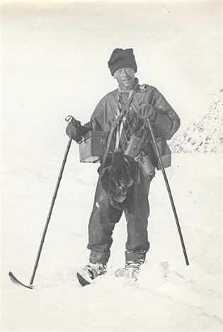 levick laden with camera and instrument cases with skis and wearing finnesko by george murray levick