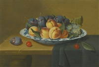 still life with peaches, plums and grapes in a wan-li porcelain dish, all upon a ledge partially draped with a green cloth by jacob van hulsdonck