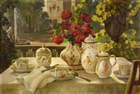 laid table with flowers and porcelain. the picture depicts a peaceful atmosphere of a summer evening after having coffee in a garden with a spouting fountain by alois zabehlicky