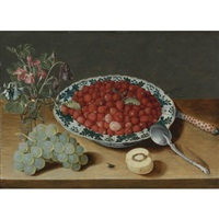 a still life with strawberries in a wan-li porcelain bowl, a bunch of grapes, a glass vase with columbines and eglantine, a silver spoon, an inlaid knife and a half peach with a fly and dragon fly on a wooden table top by isaac soreau
