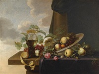 a still life with grapes, pears, a peach and roses in a waanli kraak porcelain bowl, with a roemer and a half-peeled lemon on a partly covered table top by michiel simons