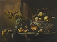 still life of fruits including peaches, grapes, a pear, and a lemon with assorted game arranged on a table ledge with a roemer and a porcelain bowl by michiel simons