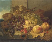 red and white grapes in a basket, with peaches, a plum, strawberries and white currents, a bird's nest and peacock feather on a stone ledge by john wainwright