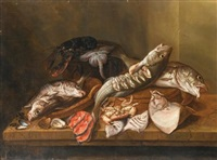 a still life with fish, an upturned crab, oysters, cockles and muscles, a ray, a lobster, turbot and haddock, all on a table in an interior by isaac van duynen