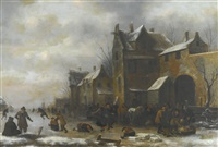 winter landscape with skaters, travellers and their horses outside a village, figures packing bundles onto a sledge by an archway on the left by klaes molenaer